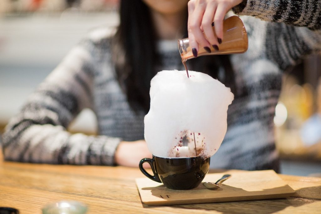 A girl pouring hot chocolate to a mug with fairy floss