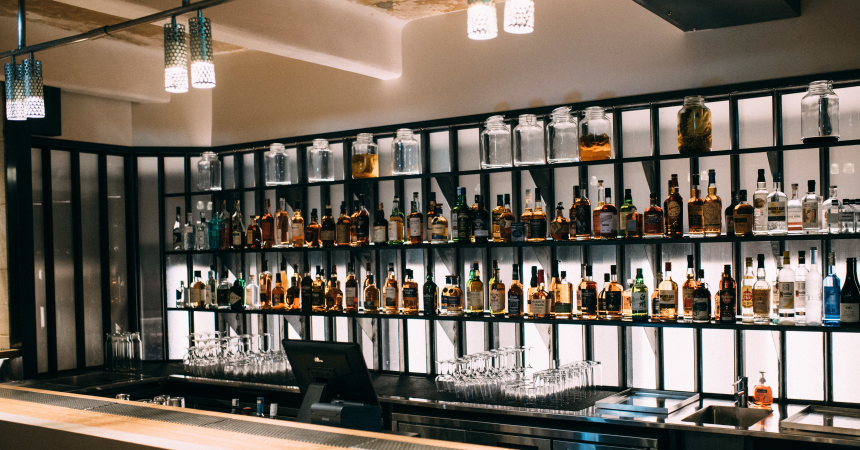 A bar with shelves stocked with wide selection of alcohol