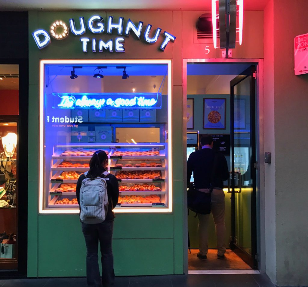 A girl looking in a doughnut show window while a man is inside buying doughnuts