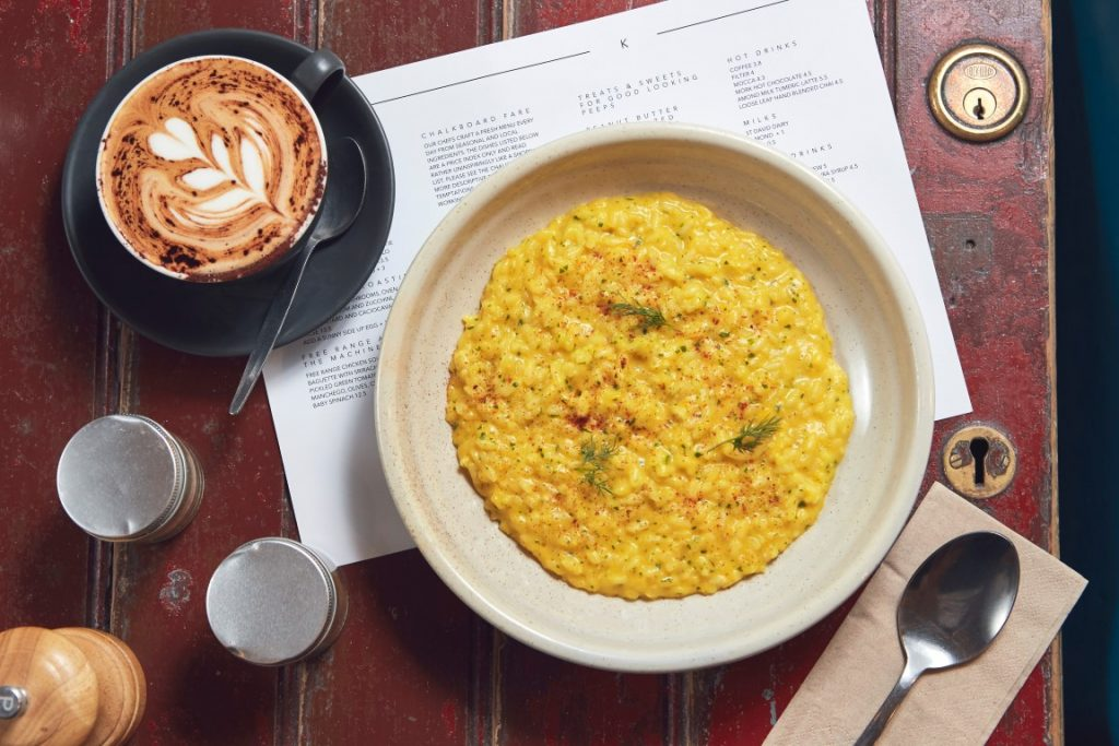 A bowl of risotto and a coffee, with a and coffee atop a meni on a wooden table