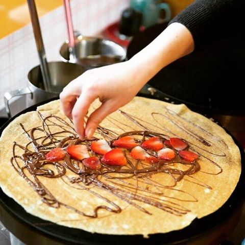 A hand putting strawberries on a pancake that is also drizzled with Nutella