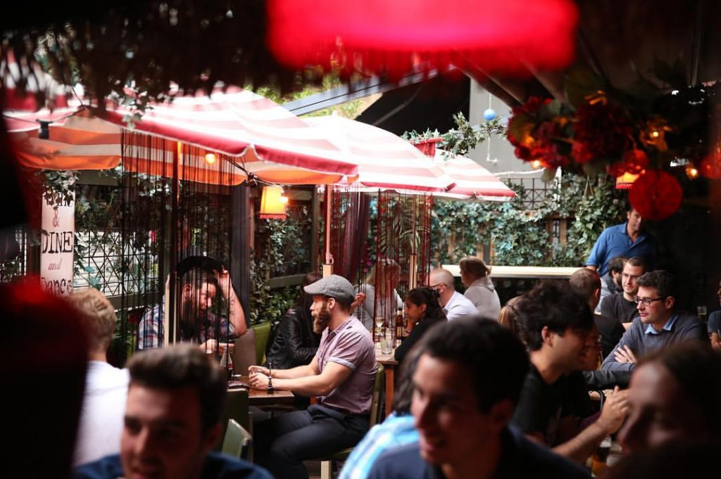 A busy bar courtyard with lots of people sitting at tables with greenery and umbrellas