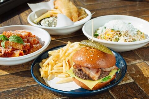 A buger and chipsm, a bowl of pasta and two other dishes on a table