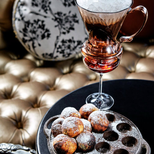 A tray of doughnuts and a cocktail on a table