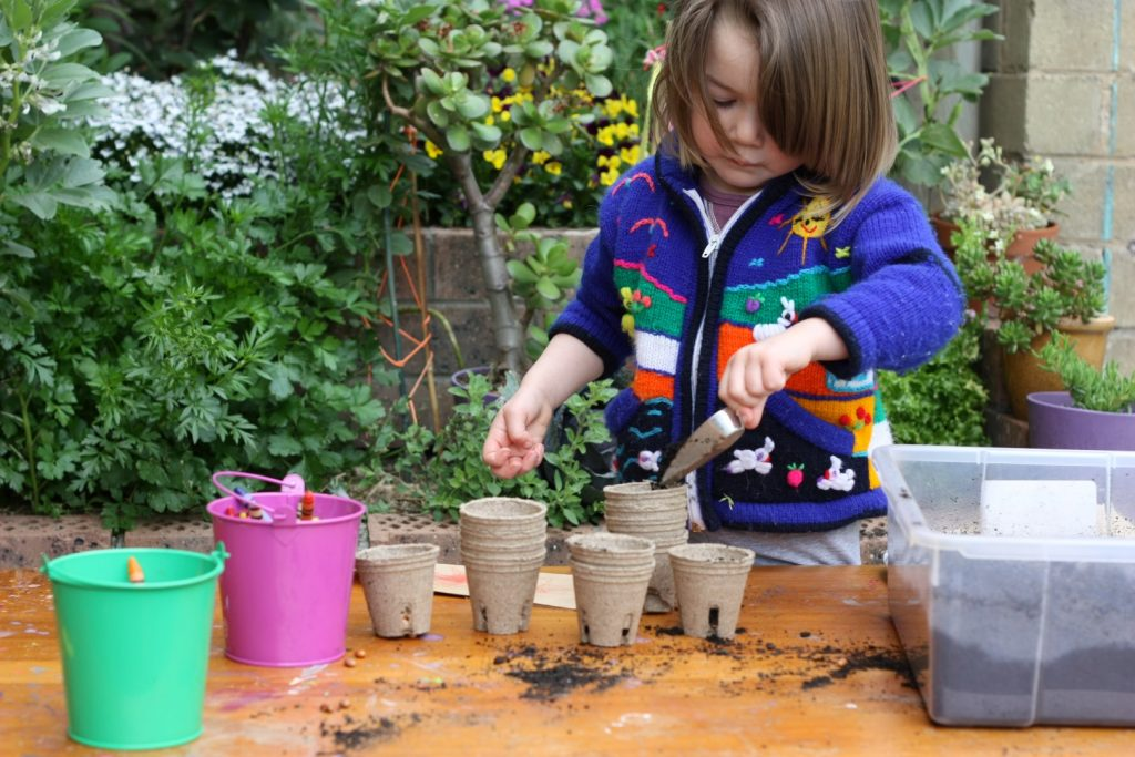 A child planning seeds in pots