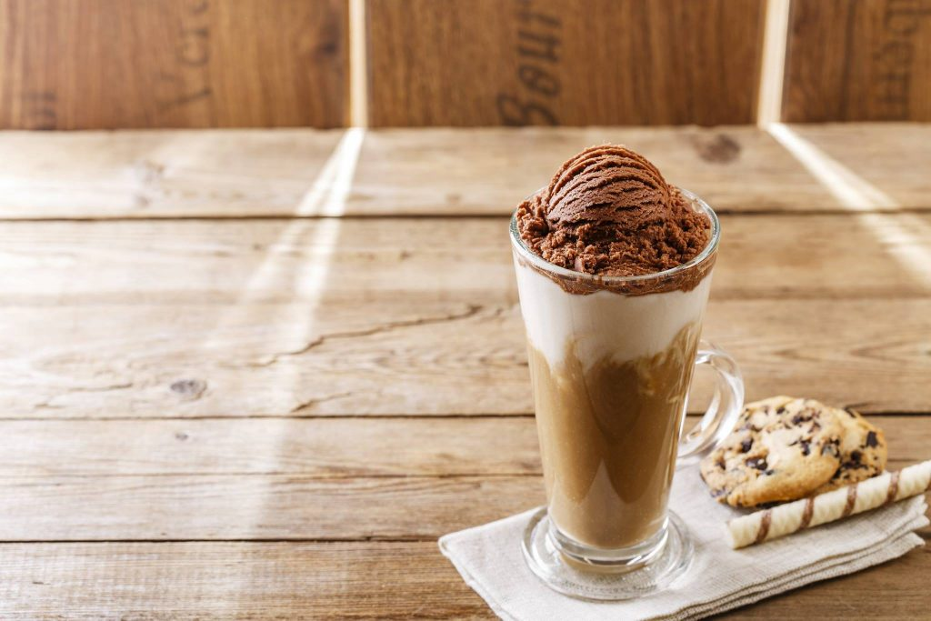 A glass of ice coffee topped with chocolate ice cream, served with cookies and chocolate stick on the side
