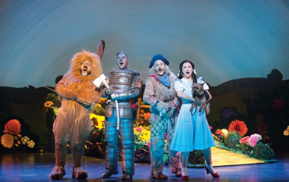 Four of the characters from Wizard of Oz standing on stage looking out to the audience - the lion, Tinman, Scarecrow and Dorothy.