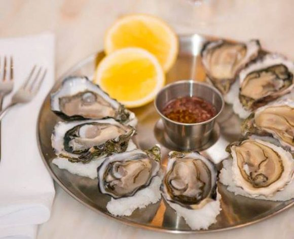 Tray of freshly shucked oysters with dipping sauce and slices of lemon, on a table.