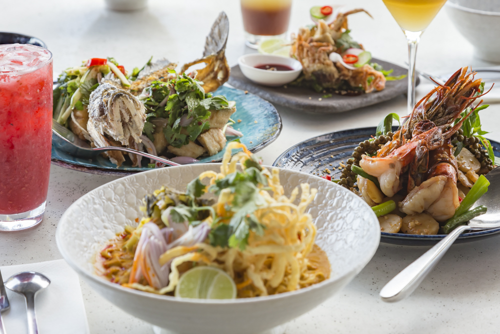 A table with several Thai dishes on it