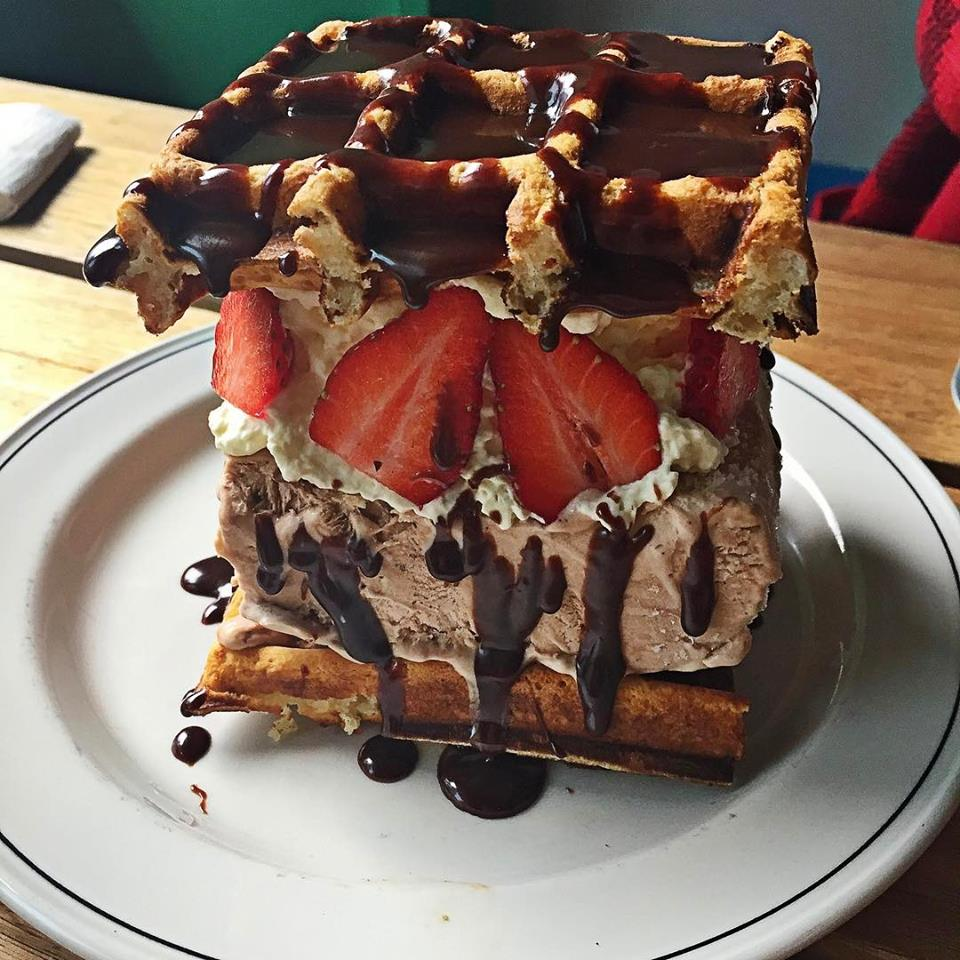 A sandwich made of waffles with chocolate icecream in the middle and strawberries on the outside