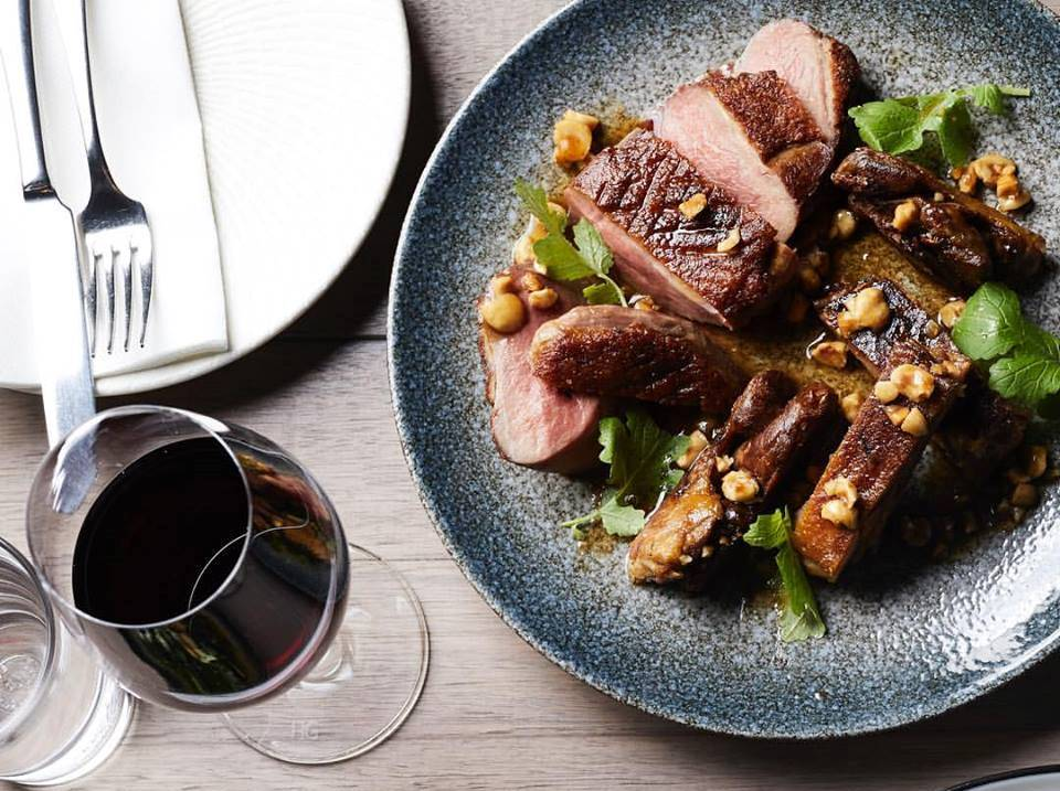 A grey plate with steak and vegetables and a glass of red wine