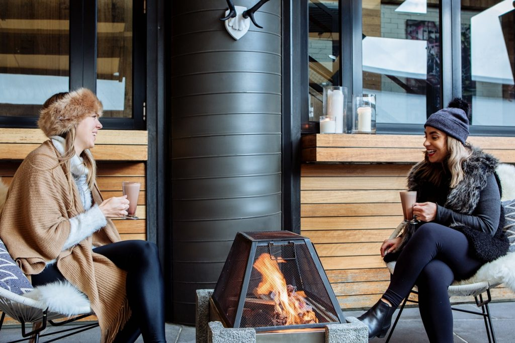 Two women sitting by the fire holding hot chocolates