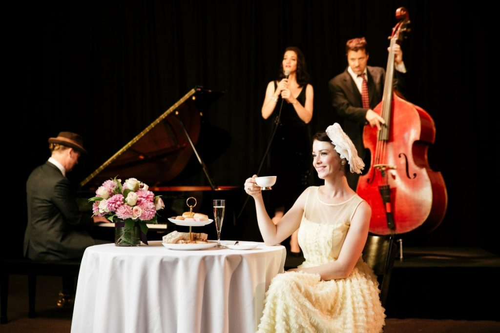 A woman in a long lemon coloured dress sits at a table drinking tea, while a man with a cello and a man playing piano are behind her