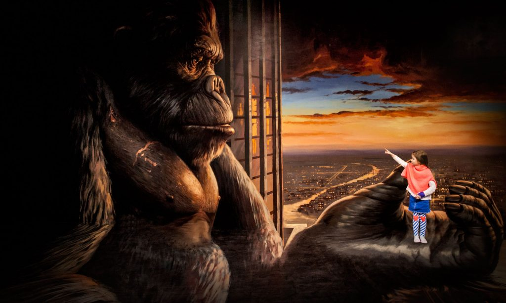 Painting of King Kong with little girl photographed standing in the palm of his hand and pointing to his face.