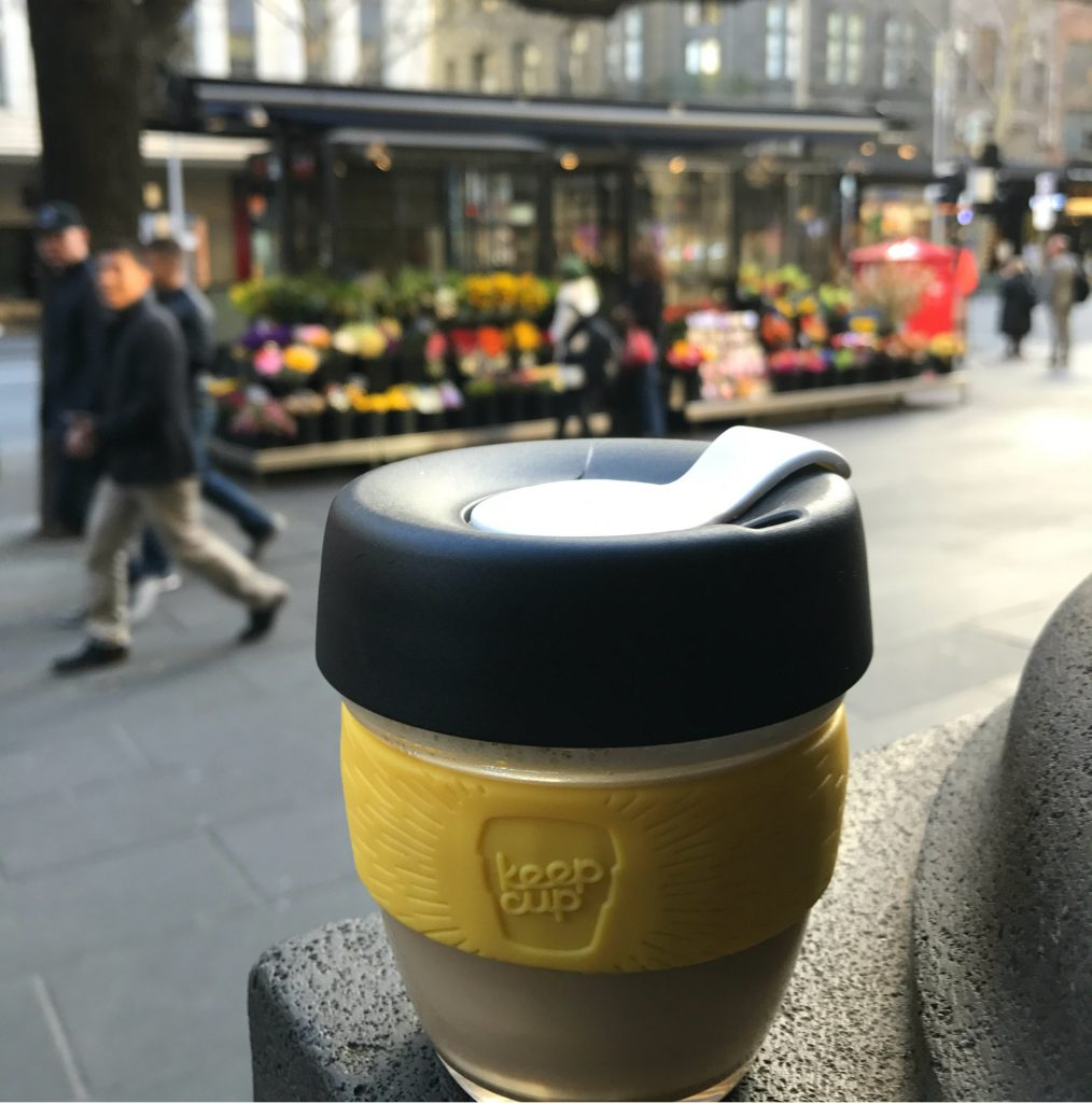 A reusable coffee cup with the scene of a street behind it