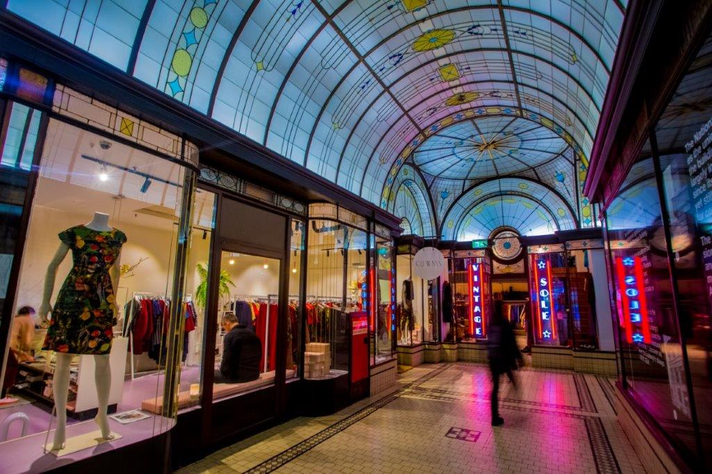 A person is walking past shops in Central Arcade, shops are lit up at photo tilts up to beautiful stained glass ceiling of the arcade.