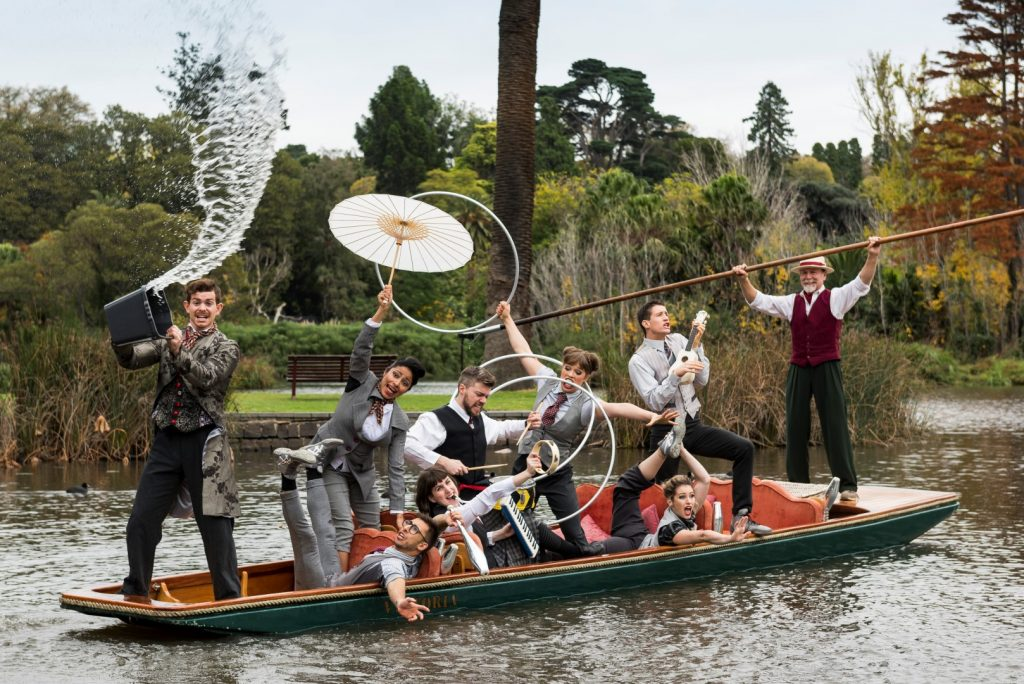 9 circus performers on a boat on a river performing tricks with hula hoops, instruments, skittles and more.