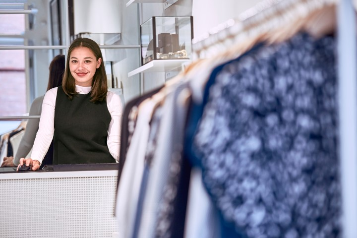 A women standing behind the counter inside a clothing store