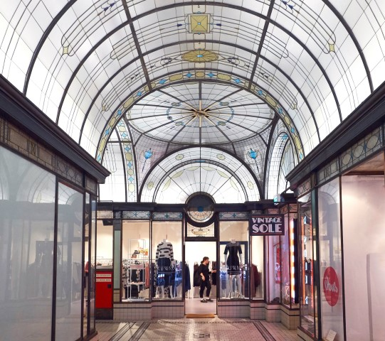 A long arcade with a domed, painted glass ceiling.