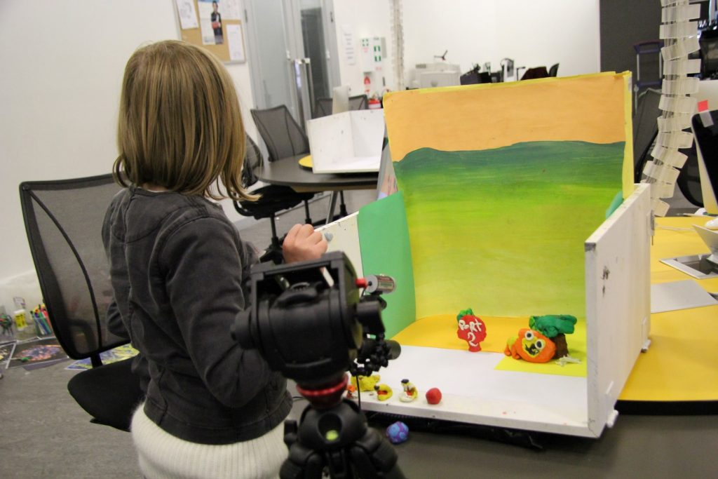A young person points a camera at plasticine models