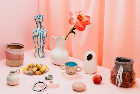 A selection of ceramic cups and vases on a pink table, with a peach coloured curtain behind them