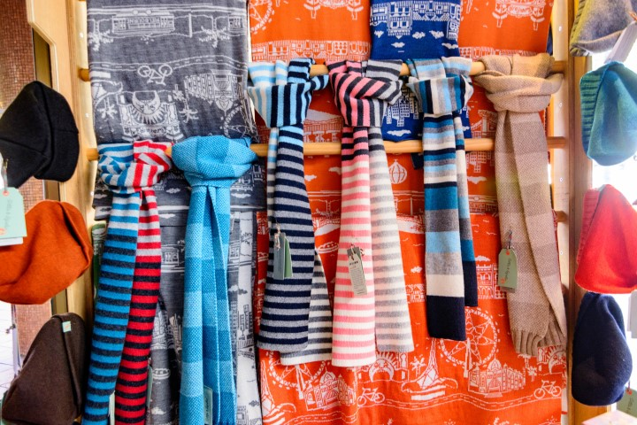 A wall with a line of colourful scarfs hanging off it