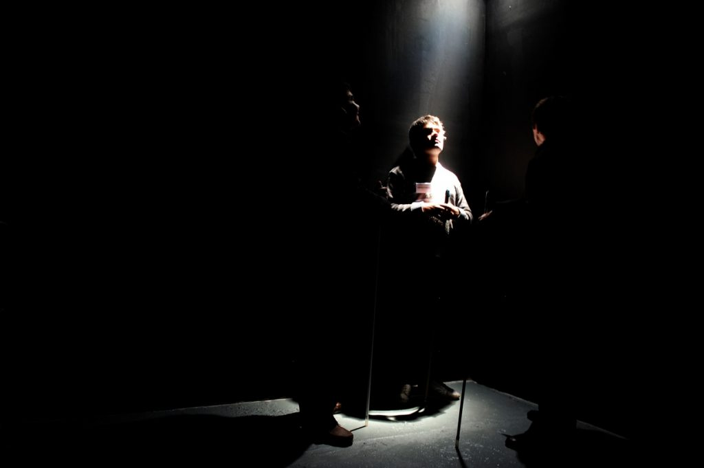 A man standing under a spotlight, accompanied by two other person