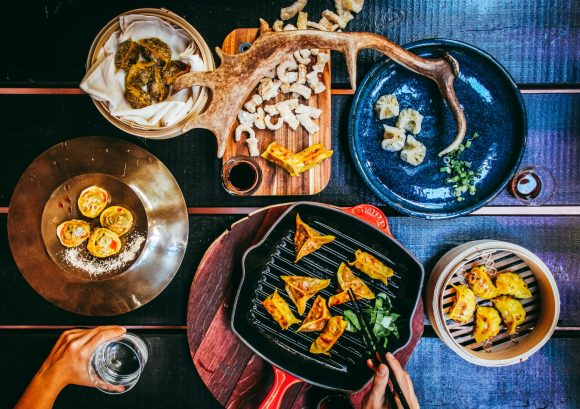 An aerial shot of various plates and skillets, with dumplings, salads and a hand reaching towards the food.