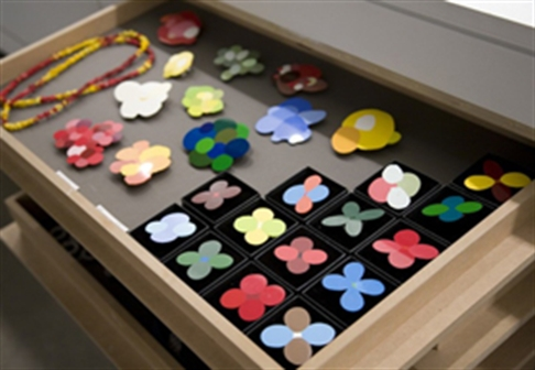 A display of several flowery accessories inside a wooden drawer