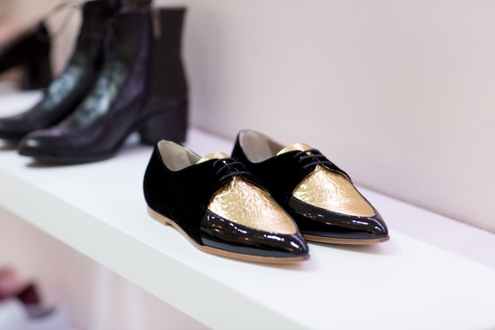 A pair of black shoes with a gold panel on the top.