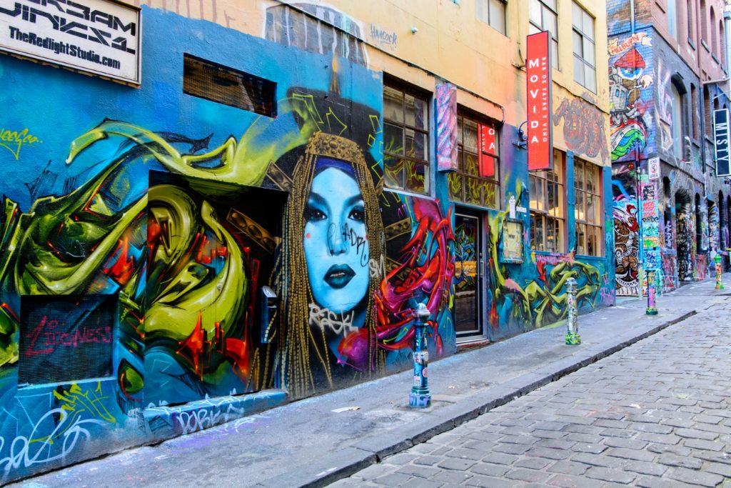 A mural on a wall in a laneway full of street art