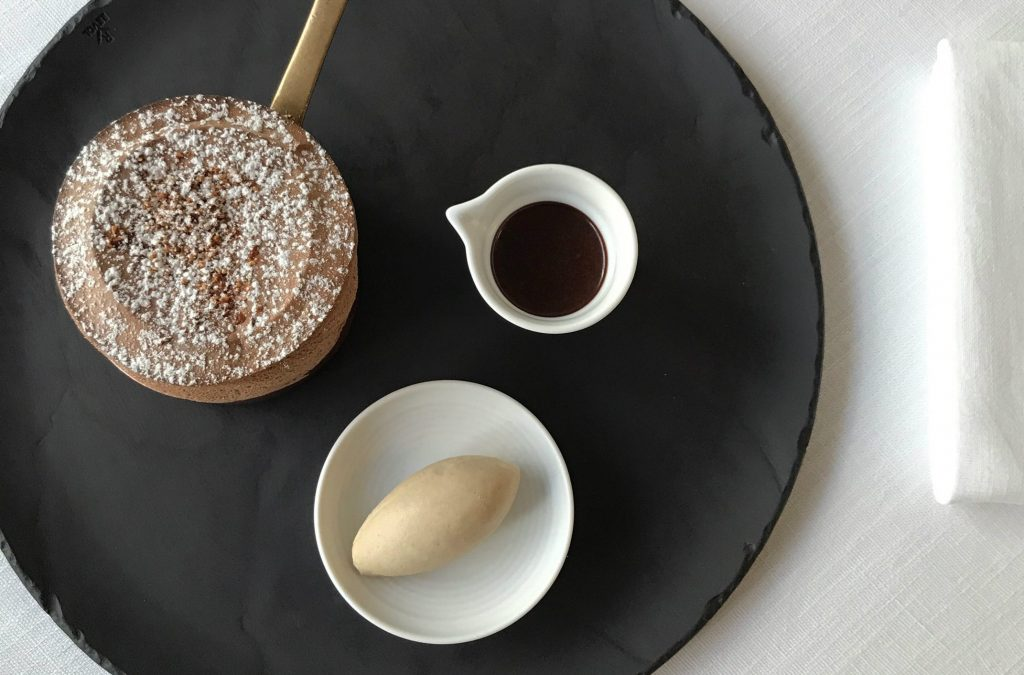 A chocolate souffle, a jug of chocolate and a scoop of ice-cream on a table