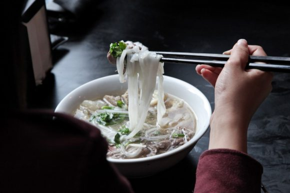 Hands holding chopsticks which are holding noodles over a bowl of soup