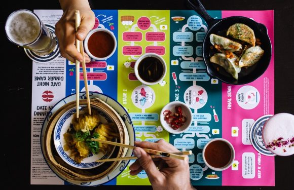 An aerial view of a table, with a colourful placemat on it. Two hands with chopsticks reach for a bowl of dumplings.