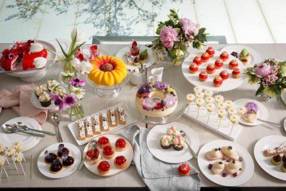A table full of trays and displays of ting cakes, tarts and other desserts, and vases of flowers