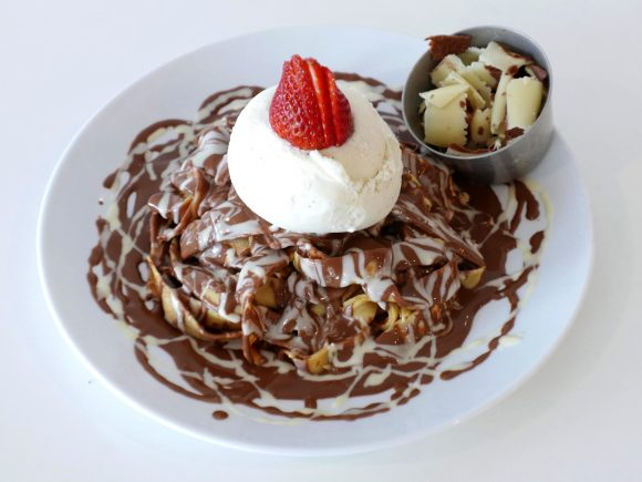 A white bowl, with pasta like crepes inside. Covered in melted chocolate and topped with ice cream and a strawberry.