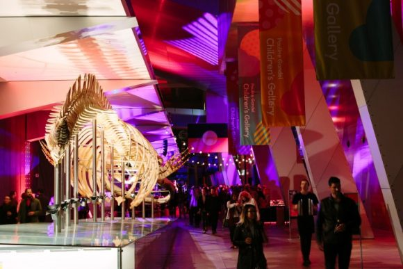 People walking past a big skeleton of a whale at an event in a museum at night