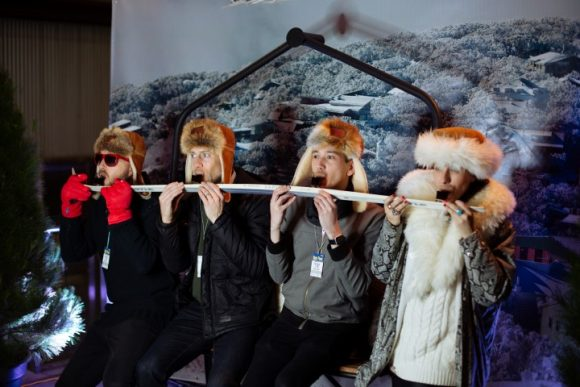 Four people dressed up in fur hats and winter clothes drinking shots off a ski