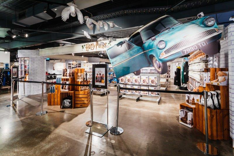 Store showing blue Ford Anglia flying through air and shelves of harry Potter merchandise in background