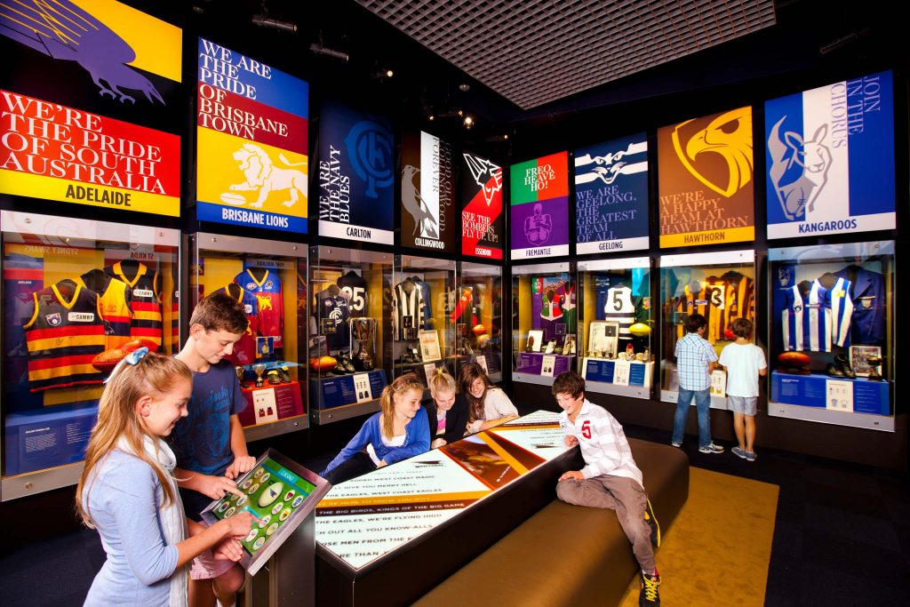 8 young boys and girls looking at displays, signs, guernseys at National Sports Museum. Lots of glass cases featuring different AFL teams uniforms, footballs and other paraphernalia.