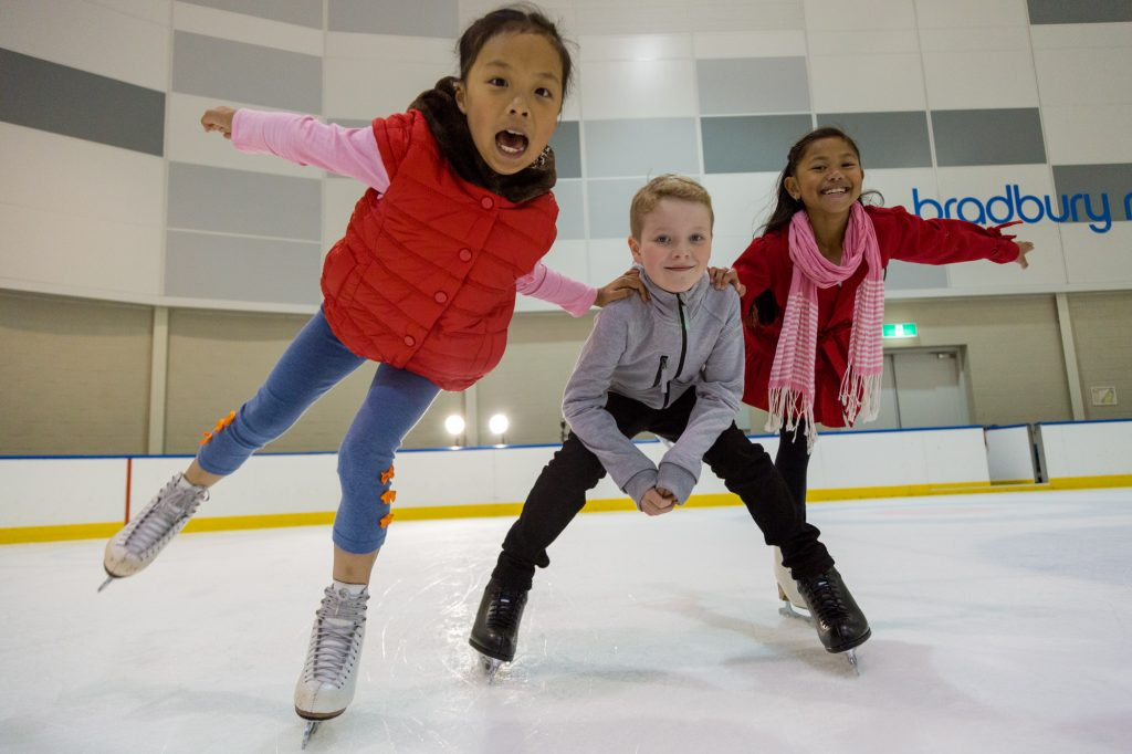 Two young girls and a boy dressed in warm wintery clothes skating together on an ice rink and smiling.