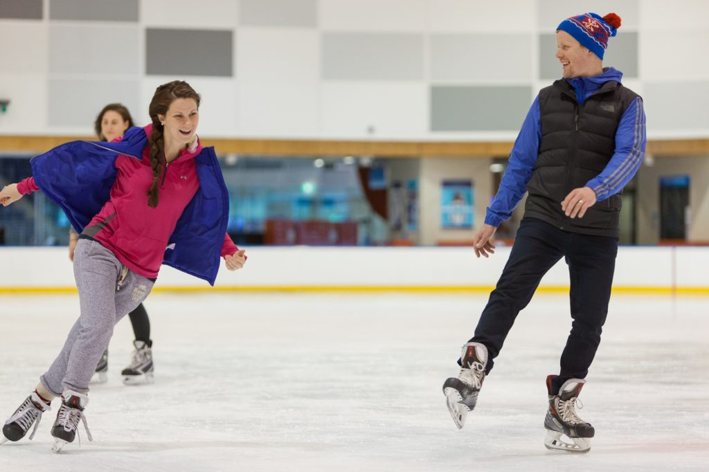 Two people ice-skating slightly off balance