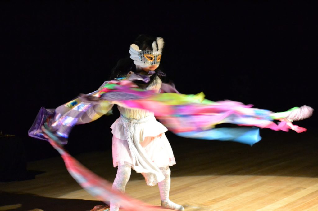 Young girl dressed up in colourful, flowing costume, white dress, silver sequined mask, dancing around a dark room.