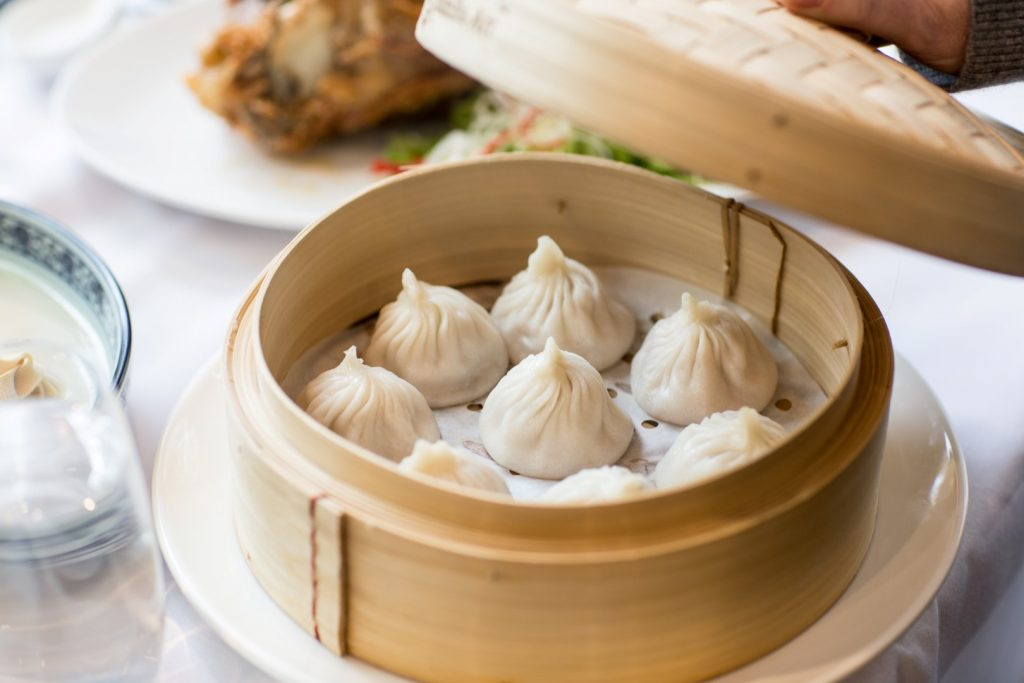 A bamboo steam tray on a white table, with the lid lifted off. Eight steamed dumplings are inside the tray.