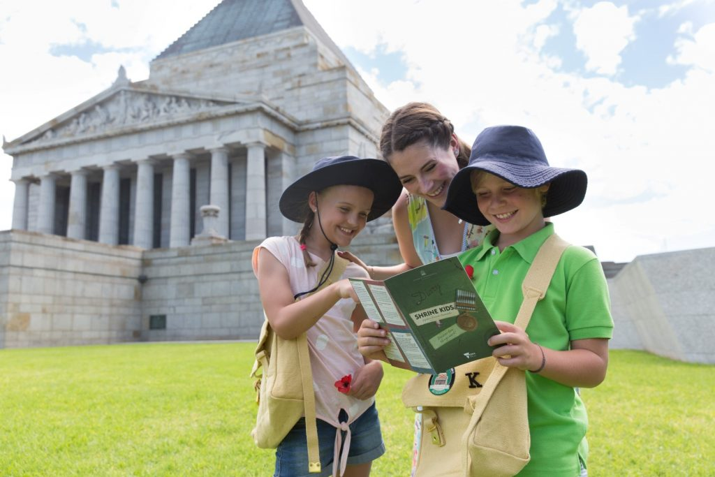 Two young children with their mother on the lawns of the Shrine of Remembrance looking through their activity pack satchel and book.