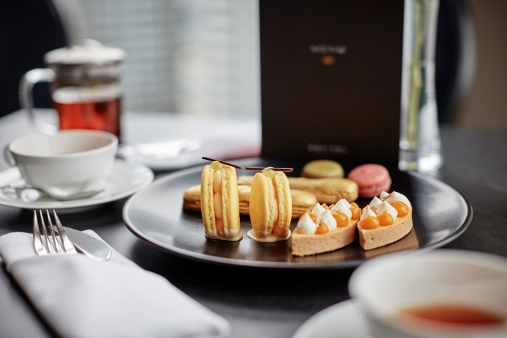 Orange macarons and pastries on a black plate, sitting on a black table
