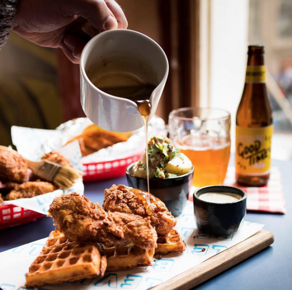 Maple syrup poured over a plate of fried chicken and waffles,