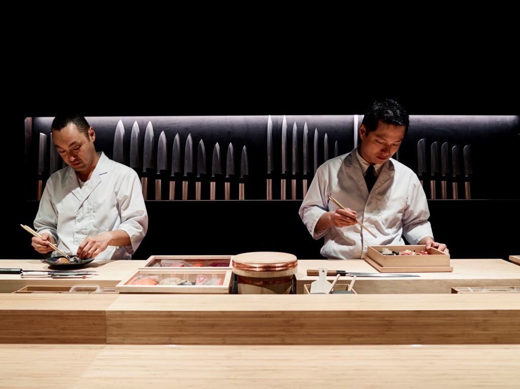 Two chefs preparing food behind the counter