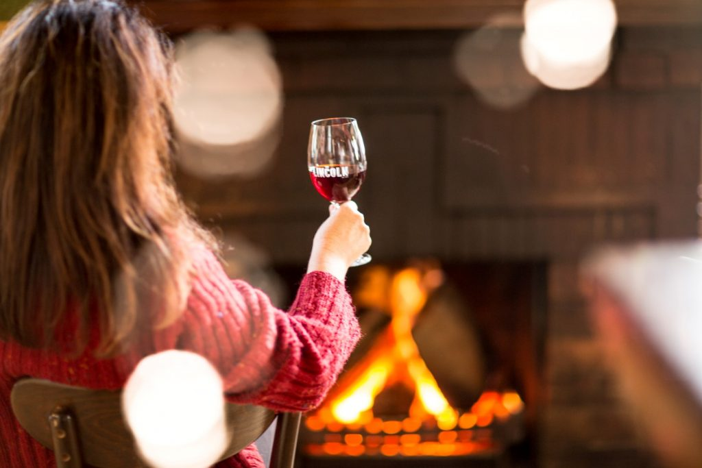 A woman sitting in front of the fire holding a glass of wine