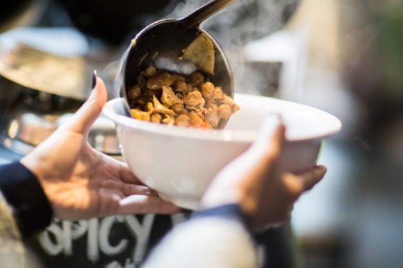 A ladle pouring soup into a bowl